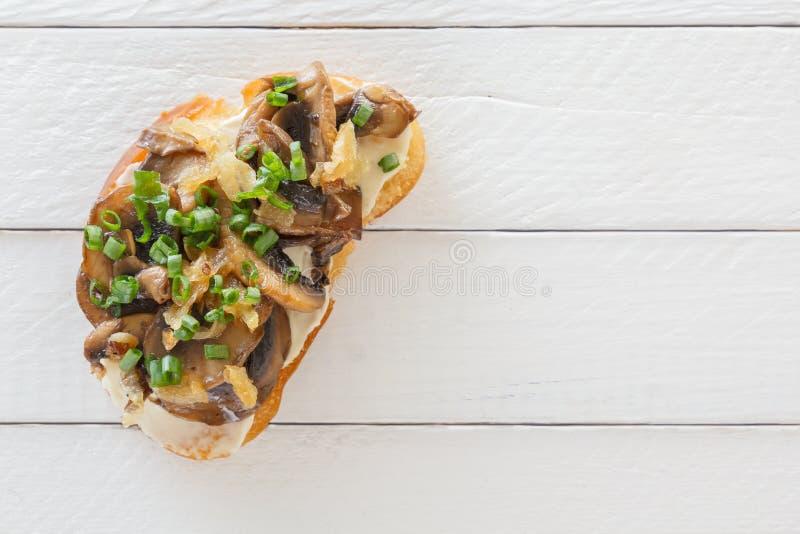 Bruschetta fresco delicioso con las setas en un fondo de madera blanco foto de archivo