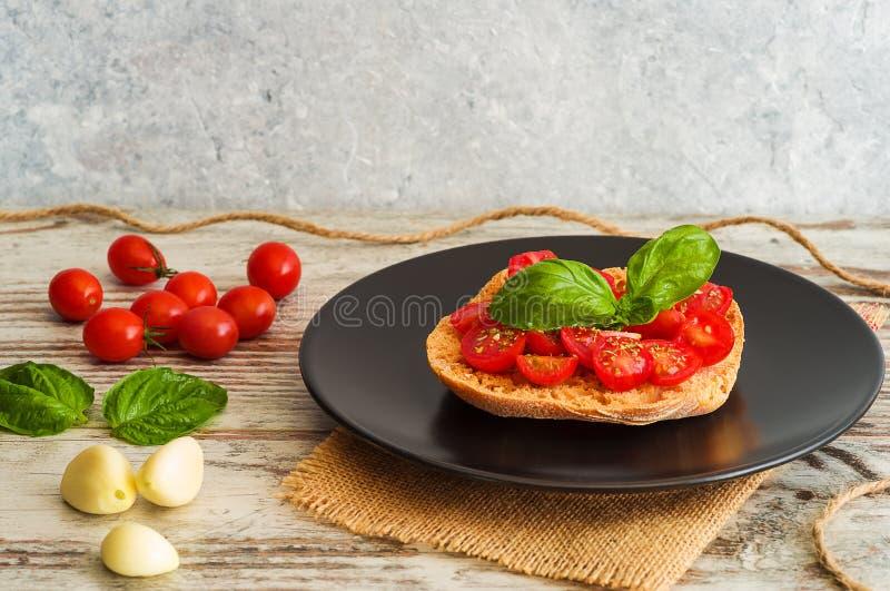Bruschetta with fresh tomato, basil and garlic on black dish. Fresh tomato bruschetta with basil and garlic stock photos