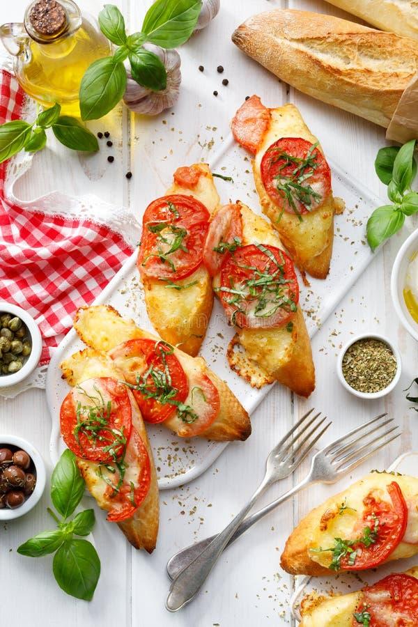 Bruschetta, gegrillte Scheiben des Stangenbrots mit Mozzarellakäse, Tomaten, Knoblauch und aromatischem Basilikum auf einem weiße stockfotografie