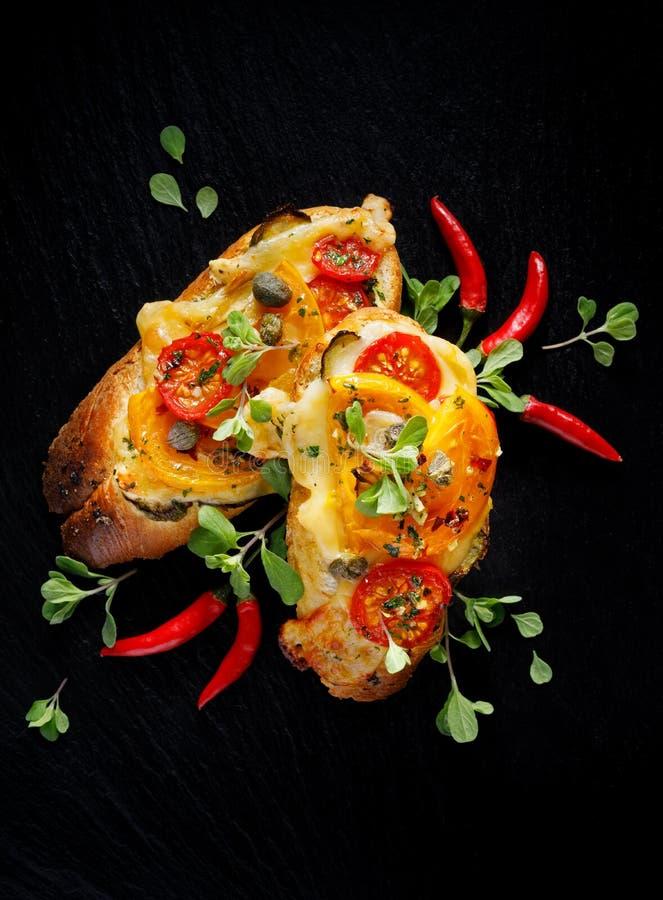 Bruschetta, geroosterde baguette met toevoeging van tomaten, kaas en kruiden op een zwarte achtergrond, hoogste mening stock afbeeldingen