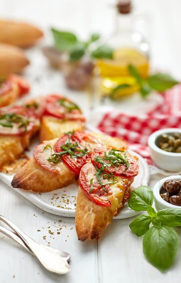 Bruschetta, geroosterde plakken van baguette met mozarellakaas, tomaten, knoflook en aromatisch basilicum op een witte houten lij royalty-vrije stock foto