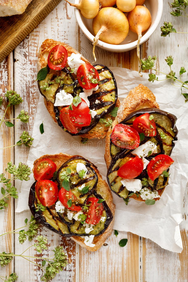 Bruschetta with grilled eggplant, cherry tomatoes, feta cheese, capers and fresh aromatic herbs on a wooden table. Delicious Medit stock photography