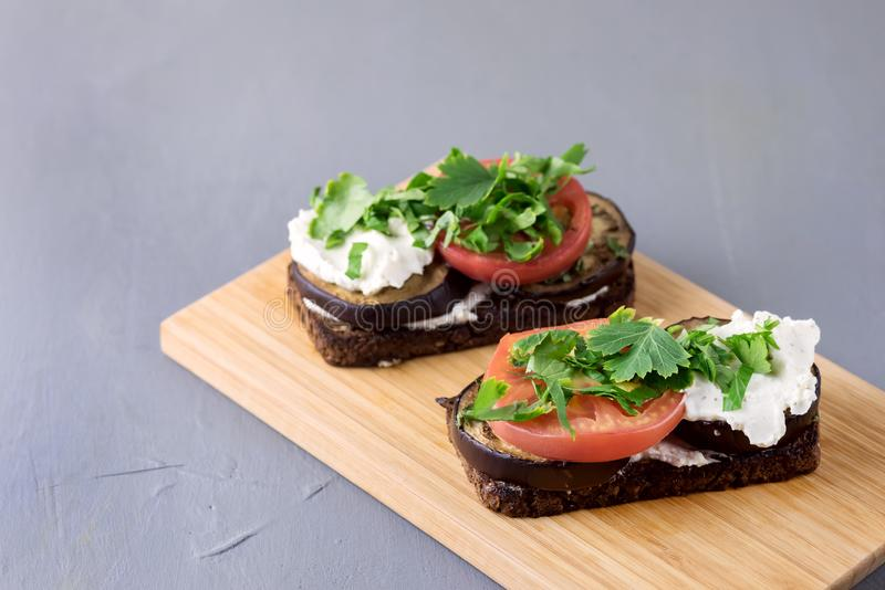 Bruschetta with Grilled Eggplant Tomatoes Cottage Cheese and Fresh Aromatic Herbs on a Wooden Tray Delicious Mediterranean stock photos