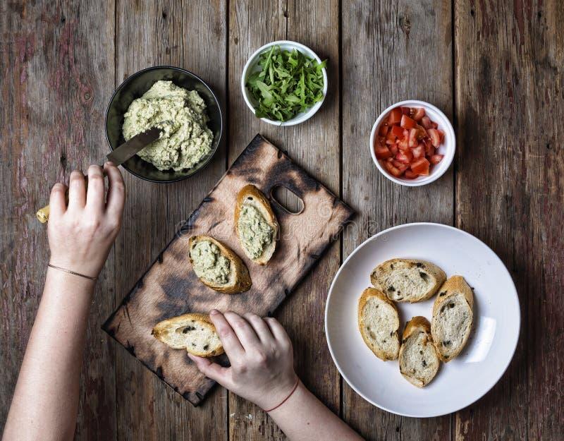 Bruschetta, het koken, meisje, het vullen, sandwich, in de zon gedroogde tomaat, stock fotografie