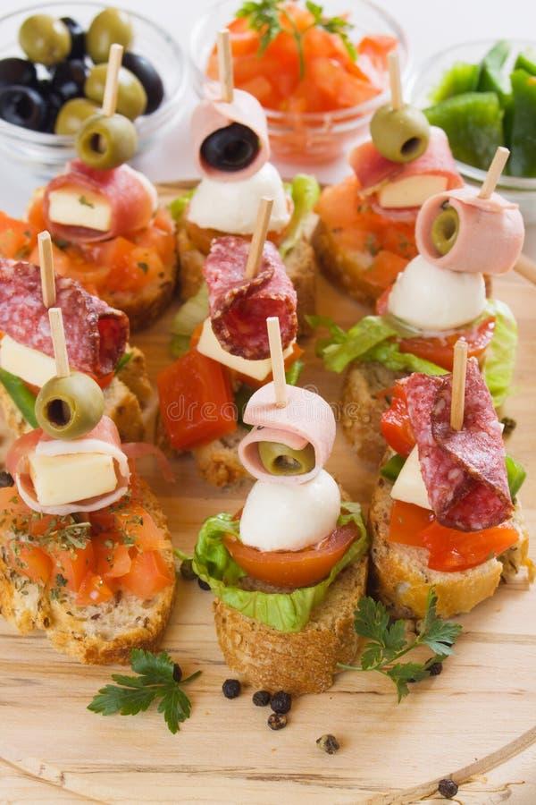 Bruschetta, italian canape. Bruschetta, italian cold buffet with tomato, olive, ham and herbs royalty free stock images