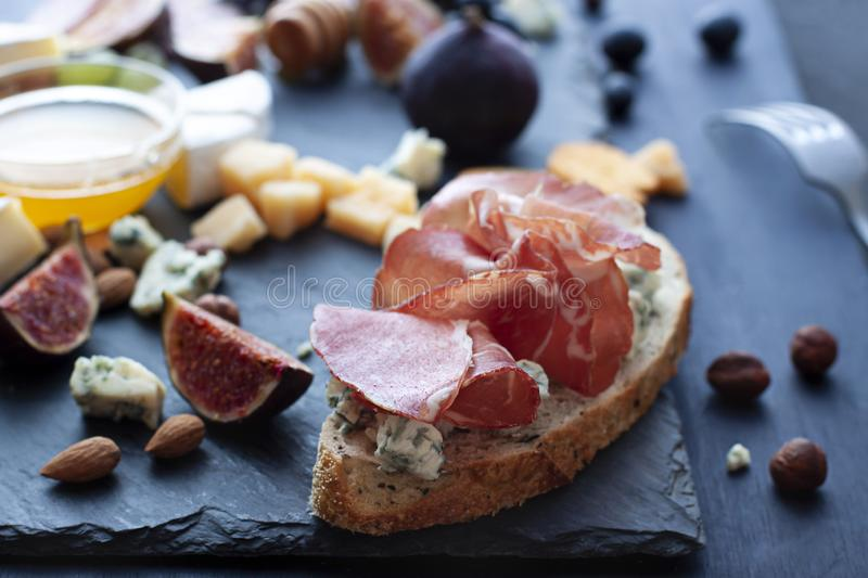 Bruschetta with Italian cured meat and dor blu cheese. Close up on the stone plate royalty free stock photography
