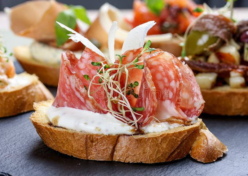 Bruschetta with Italian salami and Parmesan cheese. On stone plate stock photos