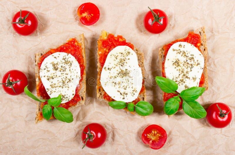 Bruschetta italiana con i pomodori ciliegia, la mozzarella & il basilico fresco fotografia stock