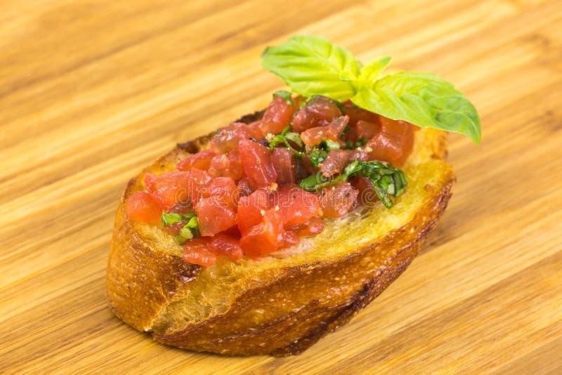 Bruschetta italiana con i pomodori ed il basilico fotografia stock libera da diritti