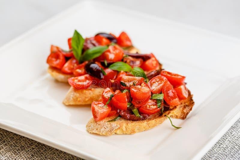 Bruschetta italiana con i pomodori, il basilico e l'oliva tagliati fotografie stock