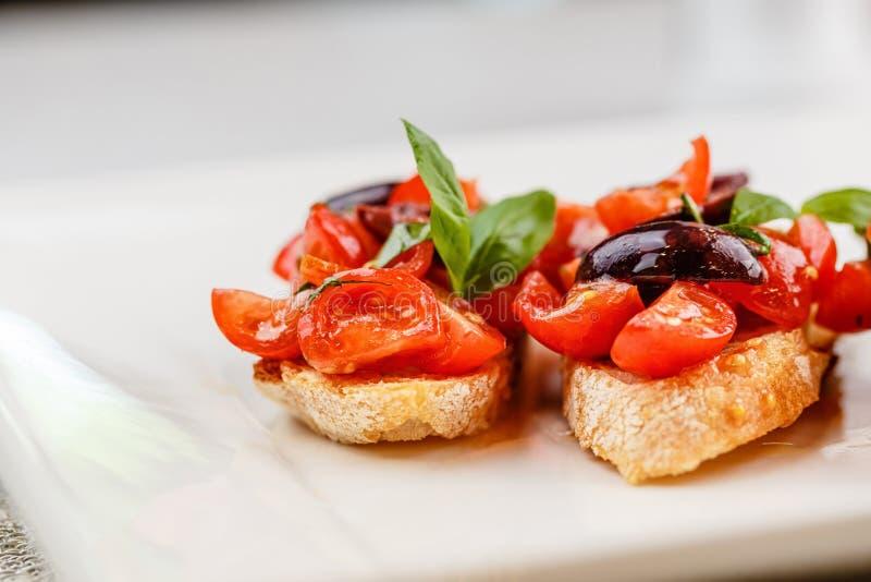 Bruschetta italiana con i pomodori, il basilico e l'oliva tagliati fotografia stock