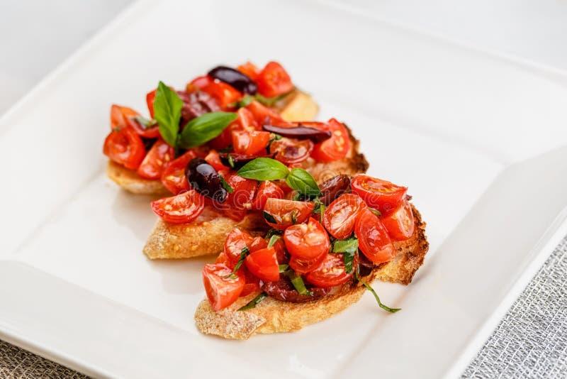Bruschetta italiana con i pomodori, il basilico e l'oliva tagliati immagini stock libere da diritti