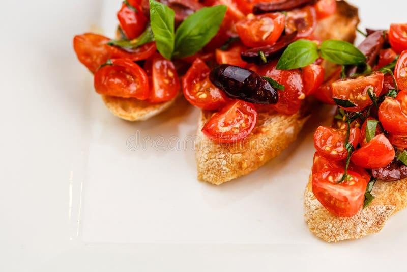 Bruschetta italiana con i pomodori, il basilico e l'oliva tagliati immagine stock