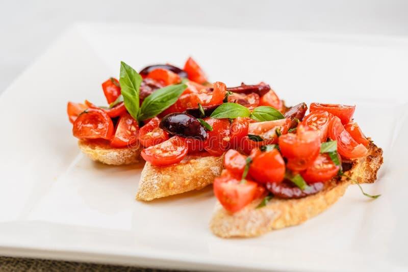 Bruschetta italiana con i pomodori, il basilico e l'oliva tagliati fotografia stock libera da diritti