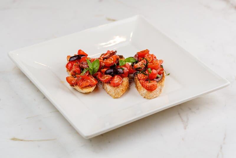 Bruschetta italiana con i pomodori, il basilico e l'oliva tagliati immagine stock libera da diritti