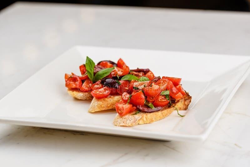Bruschetta italiana con i pomodori, il basilico e l'oliva tagliati immagini stock