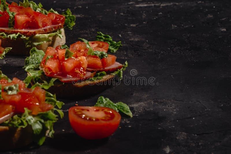 Bruschetta italiana con i pomodori, la salsa della mozzarella e le foglie tagliati dell'insalata Aperitivo o spuntino italiano tr fotografia stock libera da diritti