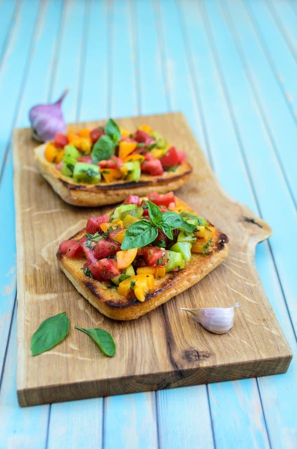 Bruschetta italiana con i pomodori tagliati e basilico sul tagliere di legno fotografia stock