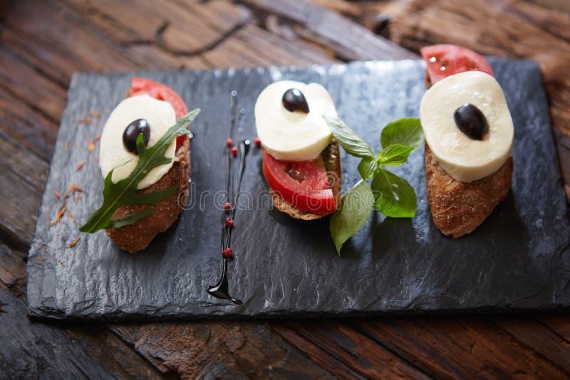 Bruschetta italiana con i pomodori tagliati, il basilico, il formaggio della mozzarella e l'aceto balsamico Caprese casalingo fre fotografia stock libera da diritti