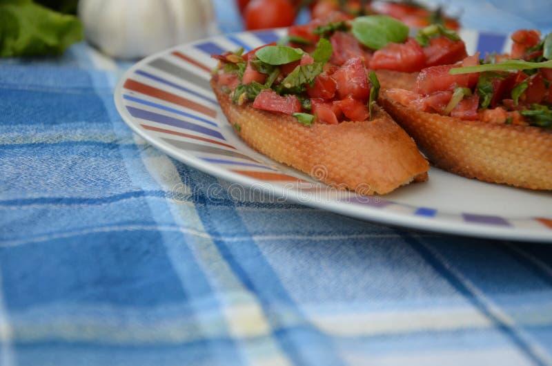 Bruschetta italiana tradizionale con il formaggio cremoso, del pomodoro ciliegia, le foglie del basilico, i capperi e l'aceto bal immagine stock