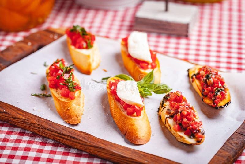 Bruschetta italiana tradizionale con il formaggio dei pomodori ciliegia, del basilico e della mozzarella sul tagliere di legno fotografia stock