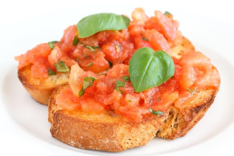 Bruschetta italiano clásico con el tomate y la albahaca foto de archivo libre de regalías