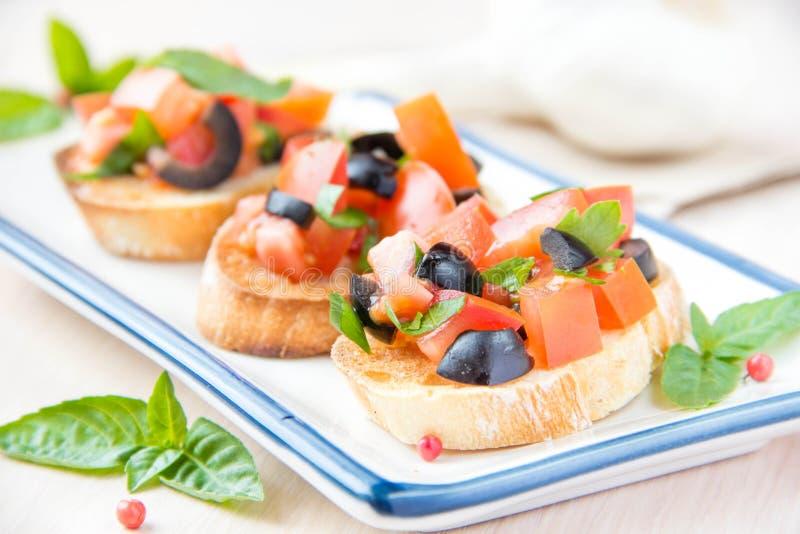 Bruschetta italiano clássico do aperitivo com tomate, manjericão e blac imagem de stock royalty free