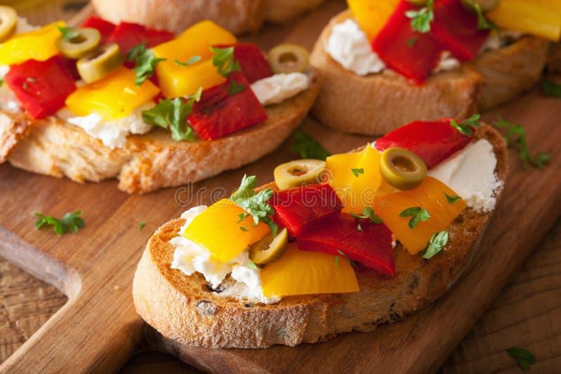 Bruschetta italiano com azeitonas roasted do queijo de cabra das pimentas imagens de stock royalty free