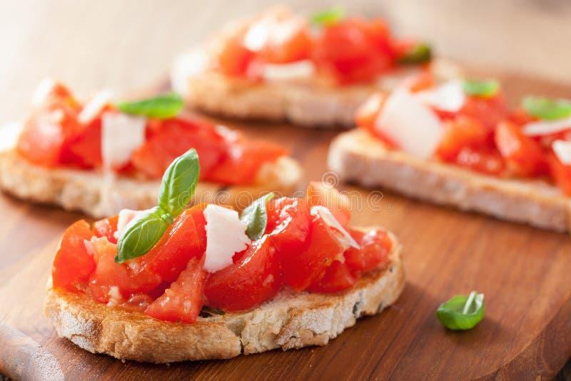 Bruschetta italiano com tomates, Parmesão, alho e azeite imagem de stock royalty free