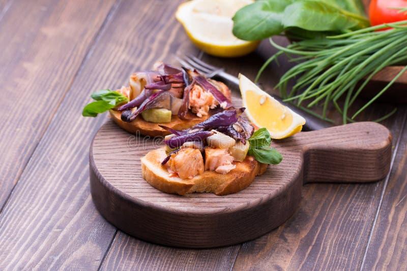 Bruschetta italiano con las verduras, los salmones, la cebolla y las hierbas asados en una tabla de cortar imagenes de archivo
