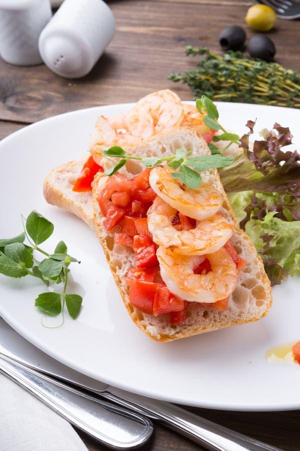 Bruschetta italiano del bocadillo con los camarones servidos en la placa blanca fotografía de archivo libre de regalías