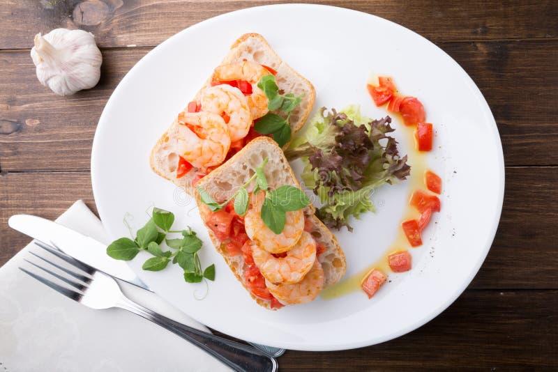 Bruschetta italiano del bocadillo con los camarones servidos en la placa blanca fotografía de archivo