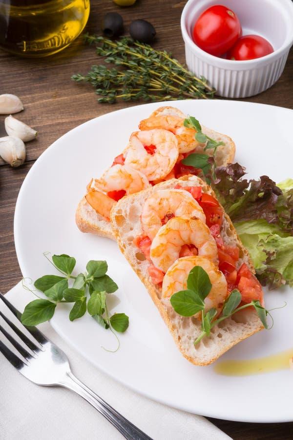 Bruschetta italiano del bocadillo con los camarones servidos en la placa blanca fotos de archivo