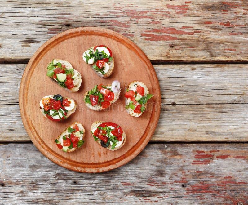 Bruschetta italiano delicioso con los tomates, el queso de la mozzarella y las hierbas asados en una tabla de cortar foto de archivo libre de regalías