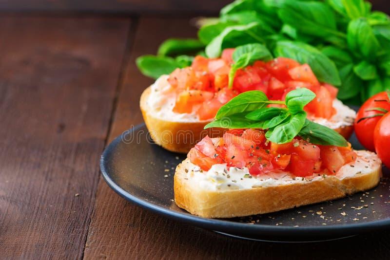 Bruschetta italiano tostado tradicional del tomate con la especia y albahaca en el tablero de madera oscuro imagen de archivo