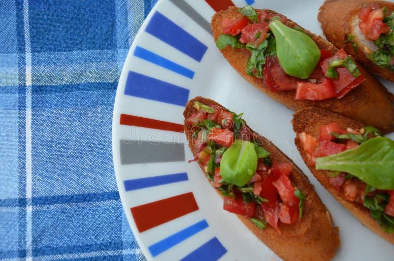 Bruschetta italiano tradicional com tomates de cereja, queijo creme, folhas da manjeric?o, alcaparras e vinagre bals?mico na plac imagem de stock