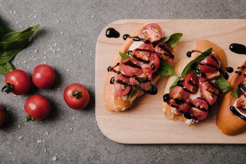 bruschetta italiano tradicional na placa de madeira, na manjericão e em tomates frescos no cinza fotos de stock