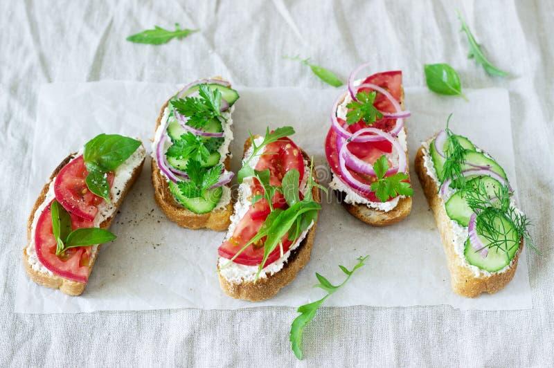 Bruschetta lub kanapki z pomidorami ogórki i kremowy ser, dekorowaliśmy z zieleniami obrazy stock