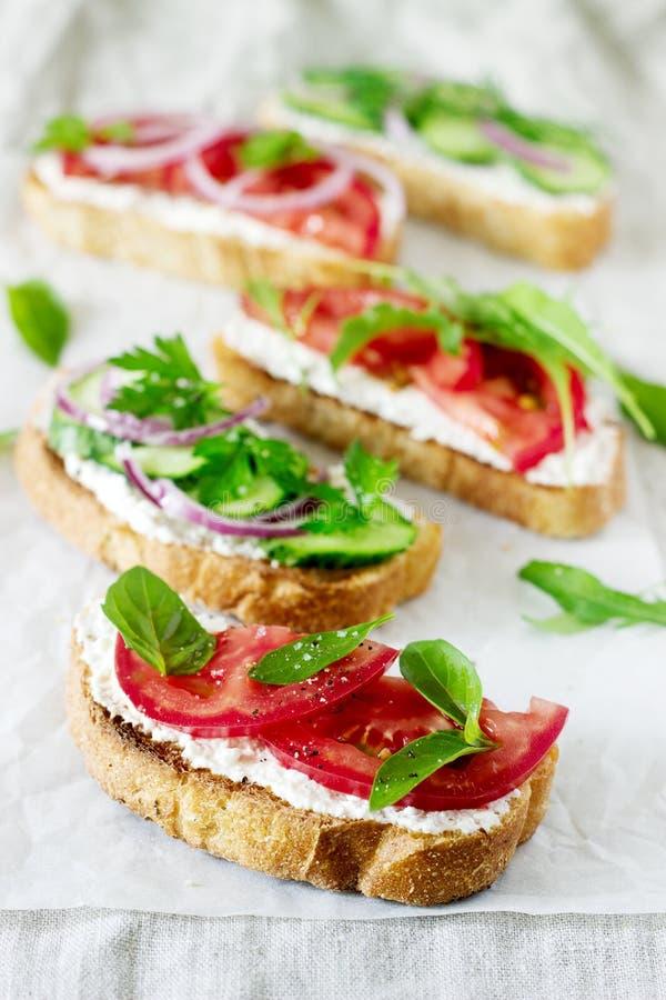 Bruschetta lub kanapki z pomidorami ogórki i kremowy ser, dekorowaliśmy z zieleniami obraz stock