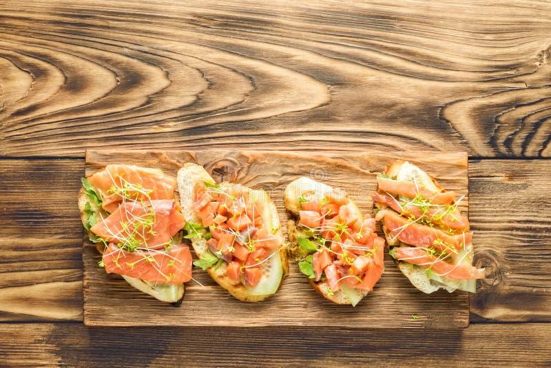 Bruschetta med den skivade fisklaxen, gurkan, arugula och unga gräsgroddar royaltyfri bild