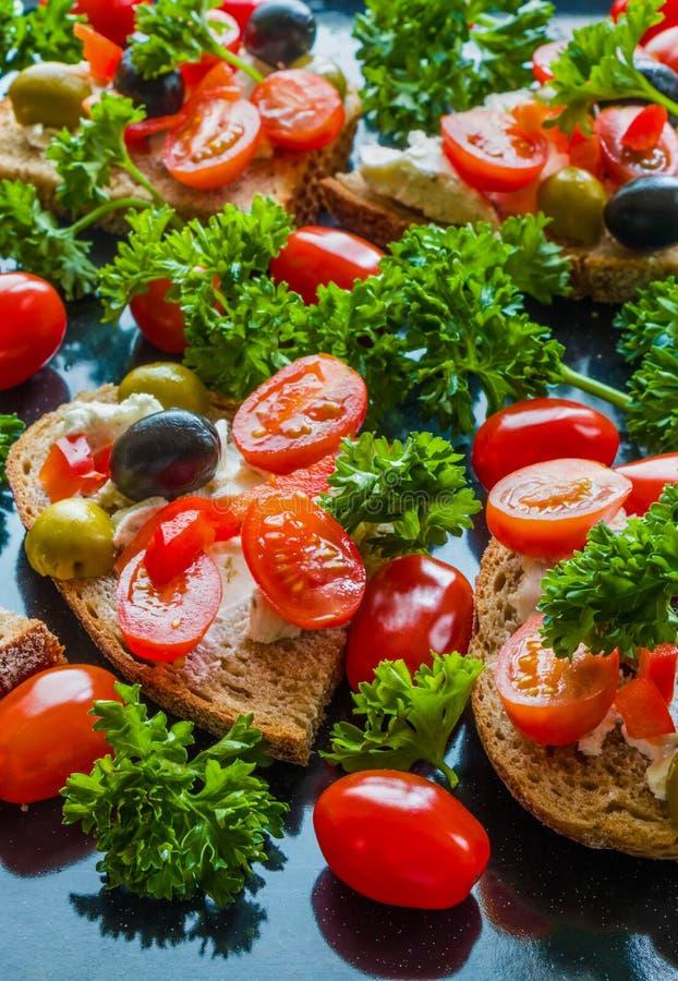 Bruschetta med gröna och svarta oliv, fetaost, körsbärsröda tomater, persilja och röd peppar på svart bakgrund arkivfoton