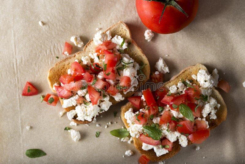 Bruschetta med grillade tomater, ost och örter arkivbild