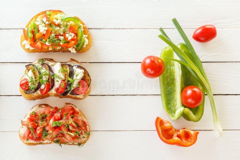 Bruschetta med ny tomater och ost, aubergine och mozzarella, söt peppar och getost på vita bräden royaltyfri fotografi