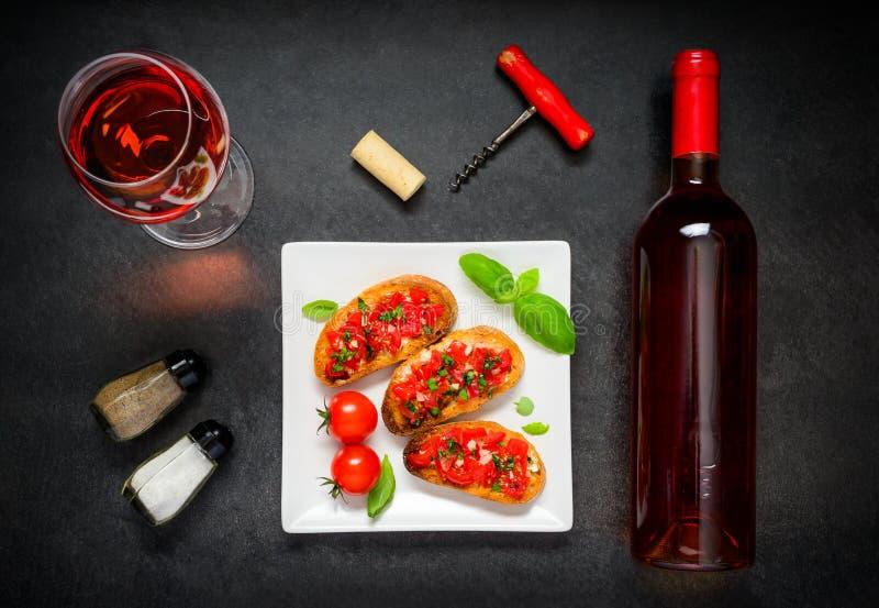 Bruschetta med Rose Wine Glass och flaskan fotografering för bildbyråer