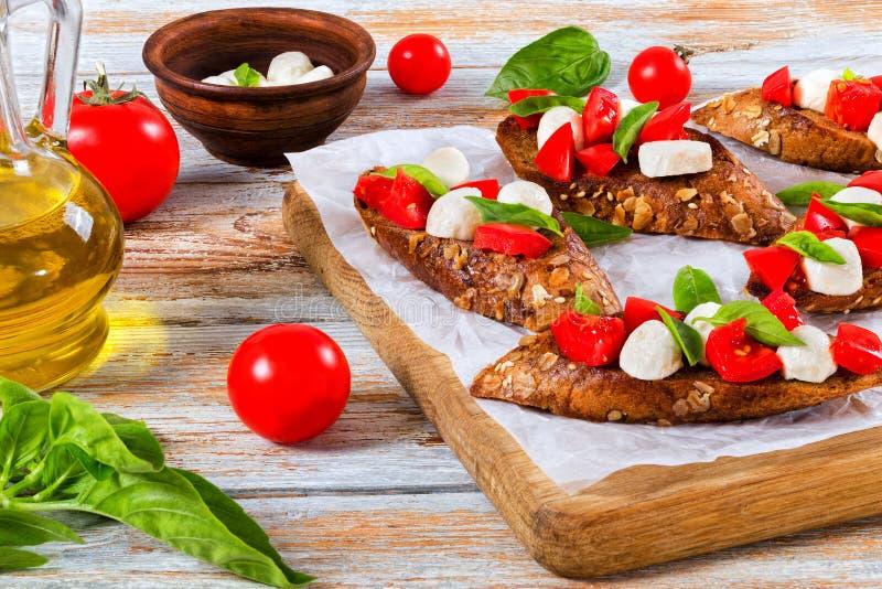 Bruschetta med tomater, mozzarellaen och basilika på rågbaguett royaltyfri bild