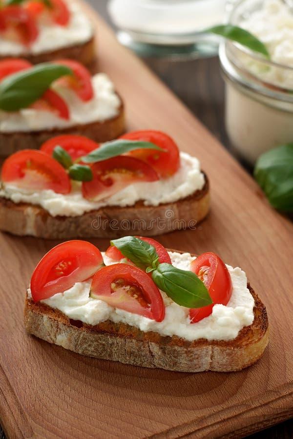 Bruschetta mediterráneo del aperitivo con queso, el tomate y la albahaca en tabla de cortar imagen de archivo