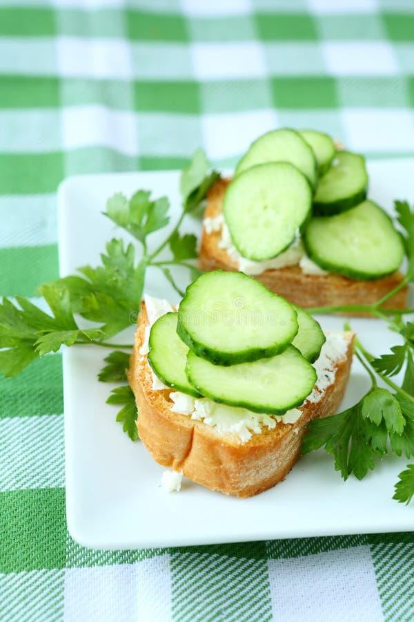 Bruschetta met kaas en verse komkommer op een plaat stock fotografie