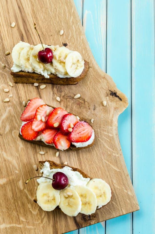 Bruschetta met kaasricotta, bessen en banaan over houten lijst stock afbeelding