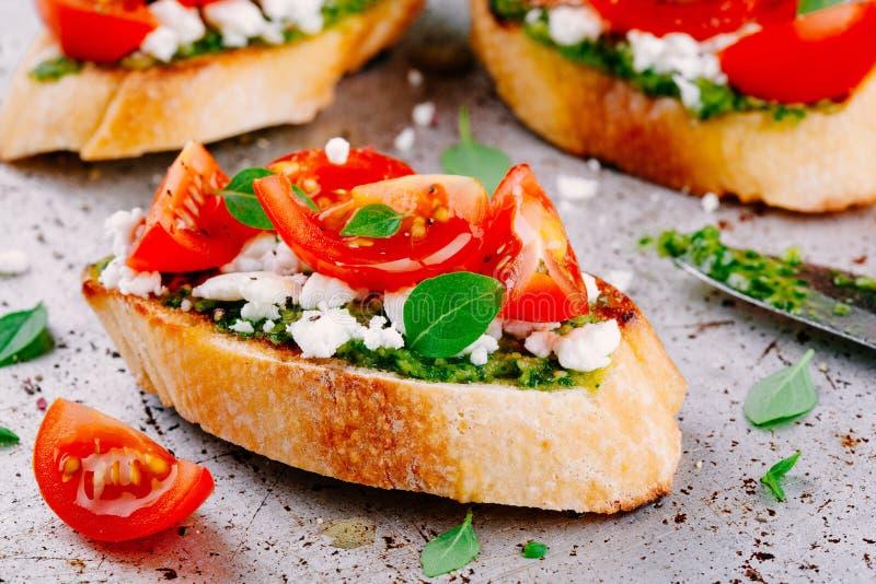 Bruschetta met pestosaus, feta-kaas, tomaten en basilicum royalty-vrije stock fotografie