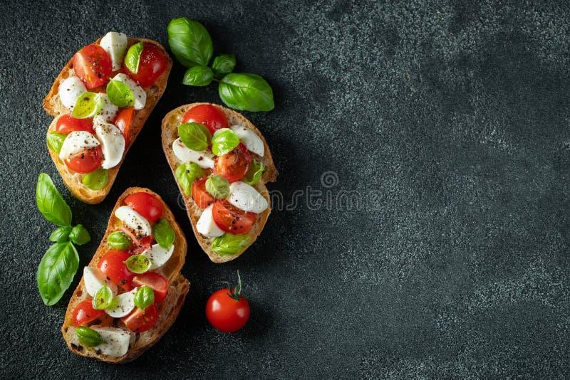 Bruschetta met tomaten, mozarellakaas en basilicum op een donkere achtergrond Traditionele Italiaanse voorgerecht of snack, antip royalty-vrije stock afbeeldingen